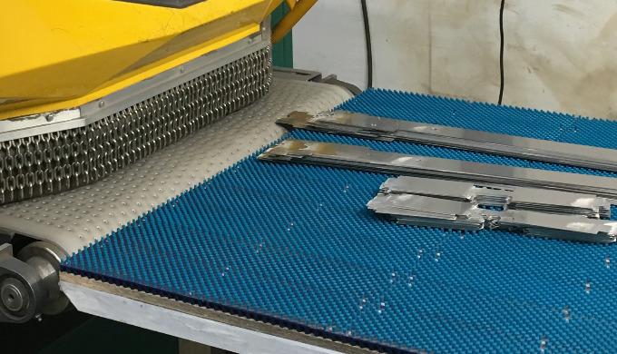 Oberflächenschutz am Ein- und Auslauf einer Entgratmaschine